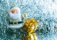 Piccolo giocattolo Santa Claus con i regali su un fondo d'argento luminoso brillante modificato Immagini Stock Libere da Diritti