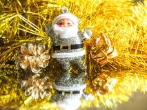 Piccolo giocattolo Santa Claus con i regali su un fondo luminoso brillante dell'oro Fotografie Stock Libere da Diritti