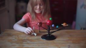 Piccolo giochi biondi della ragazza con la disposizione del sistema solare stock footage