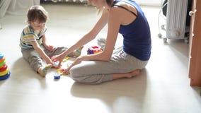 Piccolo giochi del bambino sul pavimento bianco con la mamma video d archivio