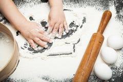 Piccolo giochi del cuoco unico con le piccole mani con farina immagine stock