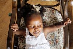 Piccolo gioco afroamericano dolce sveglio della ragazza soddisfatto dei giocattoli a casa, concetto dei bambini di stile di vita Immagine Stock Libera da Diritti