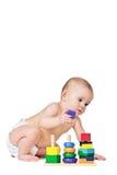 Piccolo gioco da bambini con i giocattoli su priorità bassa bianca Immagine Stock