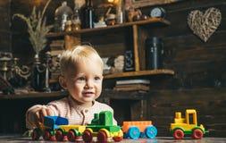 Piccolo gioco del bambino con le automobili del giocattolo in stanza dei giochi Gioco ed imparare gioco fotografia stock