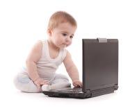 Piccolo gioco del neonato con il computer portatile Fotografie Stock Libere da Diritti