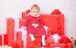 Piccolo gioco della neonata vicino al mucchio dei contenitori di regalo Regali per primo natale del bambino Celebri il primo nata fotografie stock
