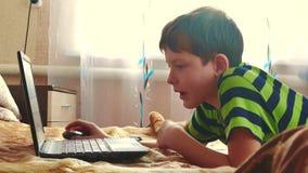 Piccolo giovane ragazzo che utilizza un taccuino in una camera da letto sta giocando il letto Internet sociale teenager di media  video d archivio