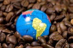 Piccolo globo sui chicchi di caffè Fotografie Stock