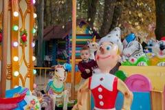 Piccolo guida divertente del ragazzo sul cavallo è un carosello della rotonda in un parco di divertimenti Bambino felice, diverte fotografia stock
