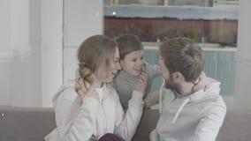 Piccolo il figlio viene ed abbraccia entrambi i genitori Bambino allegro e genitori felici Mani d'ondeggiamento della famiglia fe stock footage