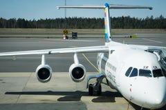 Piccolo imbarco dell'æreo a reazione nell'aeroporto con cielo blu Fotografia Stock