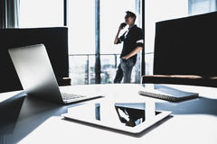 Piccolo imprenditore asiatico maschio che utilizza chiamata di telefono cellulare nell'ufficio moderno con il computer portatile  fotografie stock libere da diritti