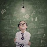 Piccolo imprenditore che esamina lampadina accesa nella classe Fotografia Stock Libera da Diritti