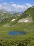 Piccolo lago della montagna con l'isola Fotografie Stock