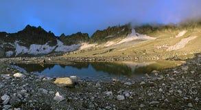 Piccolo lago della moraine in montagne di Caucaso nel primo mattino Immagini Stock