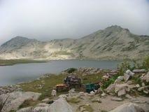 Piccolo lago in montagna alta con un cielo nuvoloso nel parco nazionale di Pirin in Bulgaria Immagini Stock