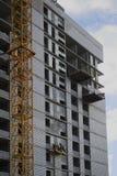 Piccolo lavoratore sulla parete di una costruzione enorme immagini stock libere da diritti