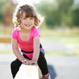 Piccolo misura i giochi della ragazza sul campo da giuoco Fotografia Stock