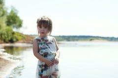 Piccolo modello adorabile che posa sul contesto del lago immagini stock