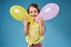 Piccolo modello allegro che posa con i palloni immagine stock libera da diritti
