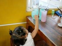 Piccolo neonata asiatica che raggiunge fuori la sua mano per le tazze di plastica variopinte sulla tavola immagine stock