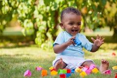 Piccolo neonato afroamericano che gioca nell'erba Fotografia Stock