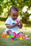 Piccolo neonato afroamericano che gioca nell'erba Immagine Stock