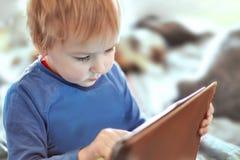 Piccolo neonato caucasico si siede sul sofà facendo uso di una compressa, schermo di contatto Capelli rossi, abbigliamento casual immagini stock