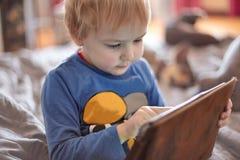 Piccolo neonato caucasico si siede sul sofà facendo uso di una compressa, schermo di contatto Capelli rossi, abbigliamento casual immagini stock libere da diritti