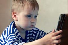 Piccolo neonato caucasico utilizza una compressa, vedente allo schermo Spesa di tempo dei bambini, automazione dei giovanotti fotografia stock libera da diritti