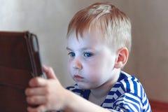 Piccolo neonato caucasico utilizza una compressa, vedente allo schermo Spesa di tempo dei bambini, automazione dei giovanotti immagini stock