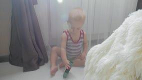 Piccolo neonato che gioca con i piccoli blocchi colourful di costruttore nella stanza sul pavimento Bambino che gioca con colorat archivi video