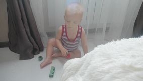 Piccolo neonato che gioca con i piccoli blocchi colourful di costruttore nella stanza sul pavimento Bambino che gioca con colorat stock footage