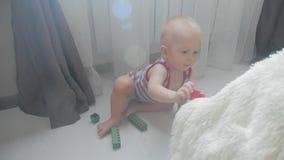 Piccolo neonato che gioca con i piccoli blocchi colourful di costruttore nella stanza sul pavimento Bambino che gioca con colorat video d archivio