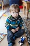 Piccolo neonato che gioca con un motociclo Fotografia Stock