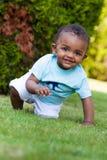 Piccolo neonato che gioca nell'erba Fotografia Stock