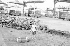 Piccolo neonato con il fronte adorabile con il salvagente sulla spiaggia Fotografia Stock Libera da Diritti