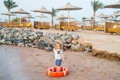 Piccolo neonato con il fronte adorabile con il salvagente sulla spiaggia Immagini Stock