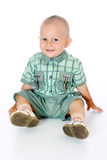 Piccolo neonato divertente che esamina macchina fotografica, seduta e sorridere Fotografia Stock Libera da Diritti