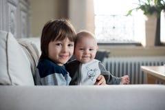 Piccolo neonato e suo il fratello più anziano, sedentesi su uno strato in sole fotografie stock
