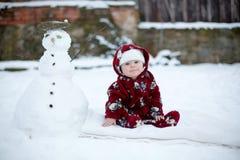 Piccolo neonato sorridente sveglio, sedentesi all'aperto nella neve Fotografia Stock