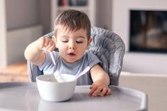 Piccolo neonato sveglio con il fronte spalmato divertente concentrato su alimento che mangia con la forcella dalla ciotola bianca fotografie stock