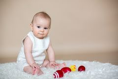 Piccolo neonato sveglio del bambino, giocante con le uova di Pasqua variopinte Fotografia Stock