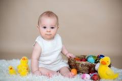 Piccolo neonato sveglio del bambino, giocante con le uova di Pasqua variopinte Fotografia Stock Libera da Diritti