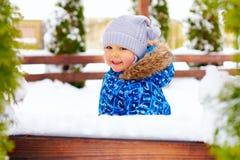 Piccolo neonato sveglio sulla passeggiata di inverno in parco immagini stock