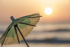 Piccolo ombrello di carta davanti alla spiaggia Mediterranea Fotografia Stock