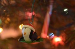 Piccolo ornamento sledding del pinguino nell'albero di Natale Immagine Stock
