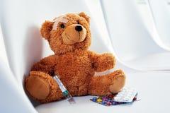 Piccolo orsacchiotto sveglio con gesso che si siede su una sedia Fotografie Stock