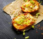 Piccolo pane tostato con formaggio fuso, cipolle di inverno, peperoncini e timo fresco su fondo nero Immagine Stock