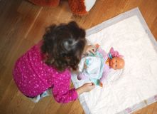 Piccolo pannolino cambiante della neonata al suo giocattolo della bambola immagini stock libere da diritti